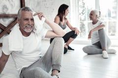 Netter strahlender Mann im Ruhestand beim Abwischen seiner Stirn mit Tuch Stockfoto