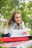 Netter Student, der auf dem Gras studiert mit ihrem Tabletten-PC liegt Lizenzfreies Stockfoto