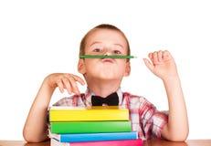 Netter Student mit Büchern und Bleistift hinter seinem Schreibtisch Stockfoto