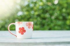 Netter Tasse Kaffee der Nahaufnahme auf unscharfer konkreter Schreibtisch- und Gartenansicht maserte morgens Hintergrund stockfoto