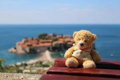 Netter Teddybär, der auf einer Holzbank mit Meer und roter Dachinsel als Hintergrund sitzt lizenzfreie stockfotografie