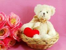 Netter Teddybär mit rotem Herzen im Korb mit rosa Hintergrund Lizenzfreie Stockbilder