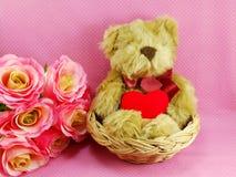 Netter Teddybär mit rotem Herzen im Korb mit rosa Hintergrund Lizenzfreies Stockfoto