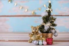 Netter Teddybär und Weihnachtsgeschenke verziert auf hölzernem Blau des Schmutzes Stockfoto