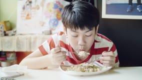 Netter thail?ndischer Junge, der Nahrung des gebratenen Reises auf der wei?en Tabelle im Wohnzimmer isst stock video