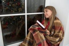 Netter Träumer Kleines Kind las Buch auf Weihnachtsabend Der kleine Leser, der im Plaid eingewickelt wird, sitzen auf Fensterbret stockfotografie