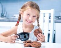 Netter trinkender Tee des kleinen Mädchens mit Plätzchen Stockfoto