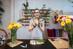 Netter unterhaltender Frauenflorist, der Blumenstrauß macht und Spaß hat Stockfoto