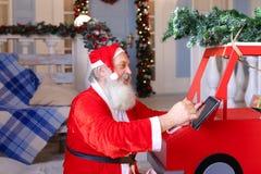 Netter Vater Christmas, das Geschenk mit Tablette vorbereitet Lizenzfreie Stockfotografie