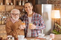 Netter Vater und Sohn, die mit Gläsern Saft aufwirft stockbild