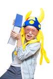 Netter verärgerter blonder Junge in einem stilvollen Hemd, das ein sehr großes blaues Buch schaut gefährlich hält Stockfotos