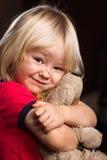 Netter verletzter Junge, der angefülltes Spielzeug umarmt Lizenzfreies Stockfoto