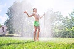 Netter Vorschülerjunge erneuern sich von Bewässerungsschlauch des Gartens auf dem FamilienLandhaus-Grasyard stockfotografie