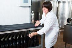 Netter weiblicher Angestellter mit Weinflaschen Stockfotografie