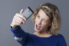 Netter weiblicher Jugendlicher, der für Selbstporträt am Handy blinzelt Stockfoto