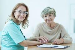 Netter weiblicher Mediziner mit Patienten Stockfotos