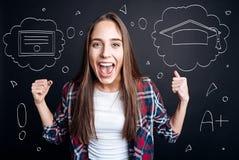 Netter weiblicher Student im Aufbaustudium, der eine Abschlussfeier hat Stockbild
