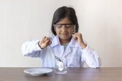 Netter Wissenschaftler des kleinen Mädchens, der ein Experiment leitet stockfoto