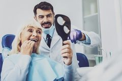 Netter Zahnarzt, der nahe seinem Besucher steht Lizenzfreies Stockbild