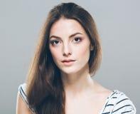 Netter zarter reiner lächelnder aufwerfender grauer Hintergrund des schönen Porträts der jungen Frau stockbild