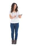 Netter zufälliger Brunette, der ihren Tabletten-PC verwendet Stockfotografie