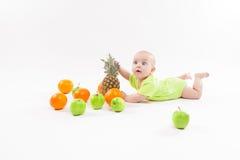 Nettes überraschtes Baby, das Frucht auf weißem Hintergrund einschließlich schaut Stockbild