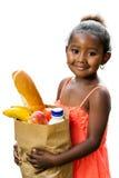 Nettes afrikanisches Kind, das Lebensmittelgeschäfte in der braunen Tasche hält stockfotografie