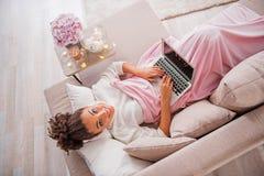 Nettes afrikanisches Mädchen, das auf Sofa mit Computer sich entspannt Stockbild
