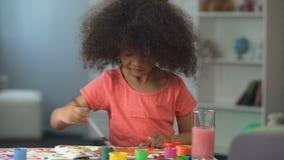 Nettes Afroamerikanermädchen, das ein Bild malt und in Kamera, Kindheit lächelt stock footage