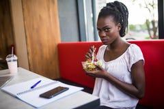 Nettes Afroamerikanermädchen, das im Restaurant isst Lächelndes Mädchen, das am Café sitzt und mit Salat auf Tabelle schaut Portr stockbild