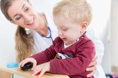 Nettes aktives Baby, das mit Spielwaren während der körperlichen Untersuchung spielt Lizenzfreies Stockfoto