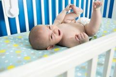 Nettes altes neugeborenes Baby des Monats legt auf sie zurück in die Krippe und schreit Lizenzfreies Stockfoto