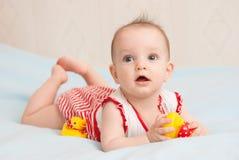 Nettes altes Sechsmonatsbaby, das mit Spielzeugente liegt Stockbilder