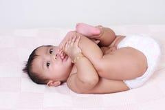Nettes asiatisches Baby, das ihre Zehen saugt Stockbilder