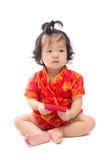 Nettes asiatisches Baby in der Klage des traditionellen Chinesen mit roter Tasche Stockbild