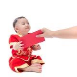 Nettes asiatisches Baby in der Klage des traditionellen Chinesen mit roter Tasche, ISO Lizenzfreies Stockbild