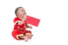 Nettes asiatisches Baby in der Klage des traditionellen Chinesen mit roter Tasche, ISO Lizenzfreie Stockbilder