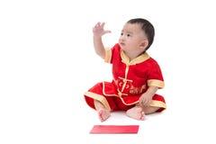 Nettes asiatisches Baby in der Klage des traditionellen Chinesen mit roter Tasche, ISO Lizenzfreies Stockfoto