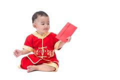 Nettes asiatisches Baby in der Klage des traditionellen Chinesen mit roter Tasche, ISO Stockbild