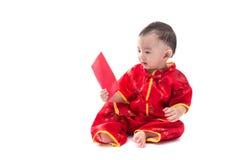 Nettes asiatisches Baby in der Klage des traditionellen Chinesen mit roter Tasche, ISO Stockbilder