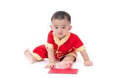 Nettes asiatisches Baby in der Klage des traditionellen Chinesen mit roter Tasche, ISO Stockfotos