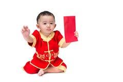 Nettes asiatisches Baby in der Klage des traditionellen Chinesen mit roter Tasche, ISO Stockfoto