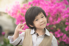 Nettes asiatisches Kind, das Mittelfinger im Park zeigt Stockbilder