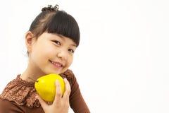 Nettes asiatisches Kind mit einer Quitte Lizenzfreie Stockfotos