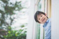 Nettes asiatisches Kind am offenen Fenster Stockbilder