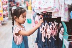 Nettes asiatisches Kindermädchen, das Kleider in der Kleidungsabteilung wählt lizenzfreie stockbilder