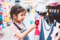 Nettes asiatisches Kindermädchen, das Kleider in der Kleidungsabteilung wählt lizenzfreies stockbild