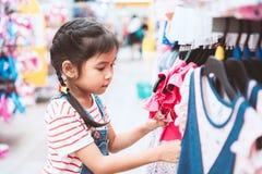 Nettes asiatisches Kindermädchen, das Kleider in der Kleidungsabteilung wählt stockbilder