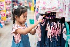 Nettes asiatisches Kindermädchen, das Kleider in der Kleidungsabteilung wählt stockbild