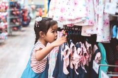 Nettes asiatisches Kindermädchen, das Kleider in der Kleidungsabteilung wählt stockfotos